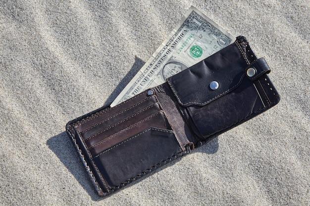 Portemonnee met geld in het zand. contant geld opnemen concept Premium Foto