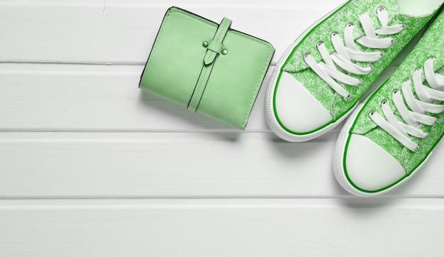 Portemonnee, sneakers op een witte houten tafel