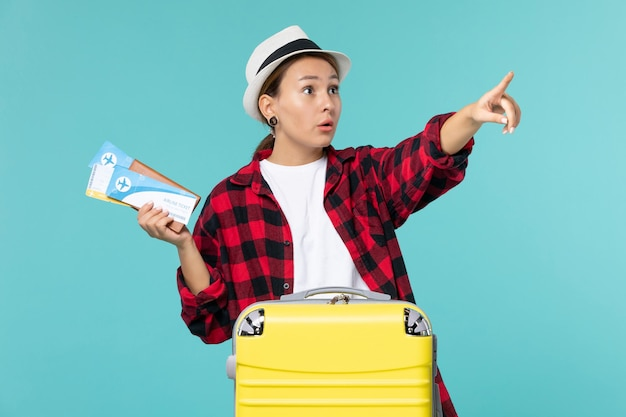 Portemonnee van de vooraanzicht de jonge vrouwelijke holdings met kaartjes op blauw bureau