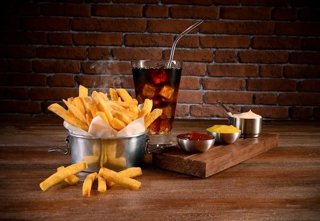 Portie frietjes met mayonaise, ketchup, mosterd en frisdrank