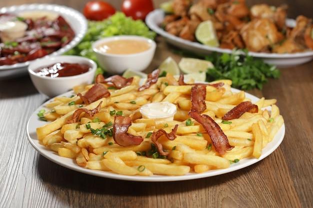 Portie frietjes met spek. sla, groene ui, tomaat, ketchup en mayonaise.