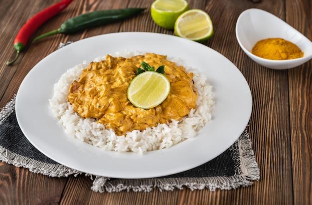 Portie kipcurry gegarneerd met rijst en verse limoen