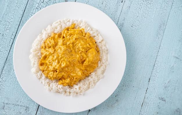 Portie kipcurry gegarneerd met rijst