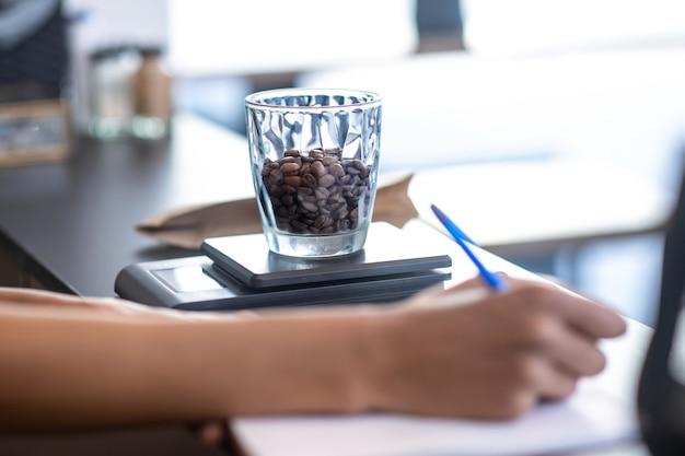 Portie, koffiebonen. smakelijke koffiebonen in schoon transparant glas op schalen in de buurt van vrouwelijke schrijven hand op teller
