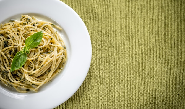 Portie pasta met pestosaus en basilicumblad
