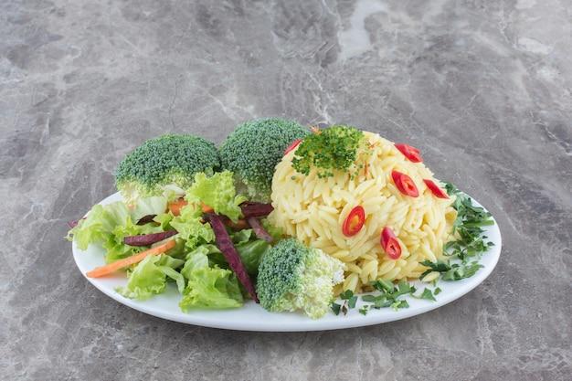 Portie pilau gegarneerd met gehakte peper, kool, bladgroente, wortel en broccoliestukjes op een schaal op een marmeren ondergrond