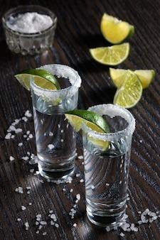 Portie tequila, omlijst met een zoutrandje met schijfje limoen in hoge borrelglaasjes