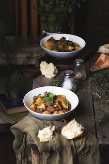 Portie traditioneel iers rundvlees en guinness-bierstoofpot met wortelen, aardappelen en doperwten