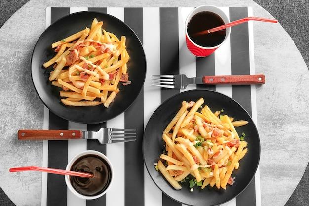 Porties heerlijke frietjes en cola op eettafel