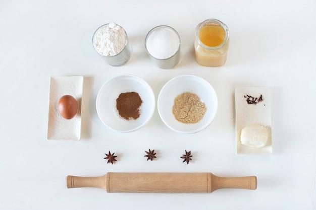 Porties ingrediënten voor het maken van koekjes, bloem in een glas, suiker, honing, boter, steranijs, ei, caoritsa, gember, steranijs