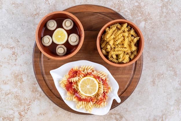 Porties pasta met een kom champignons op marmeren oppervlak. Gratis Foto