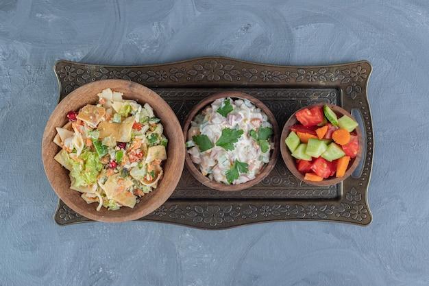 Porties van gemengde groente-, olivier- en herderssalades in houten kommen op marmeren tafel.