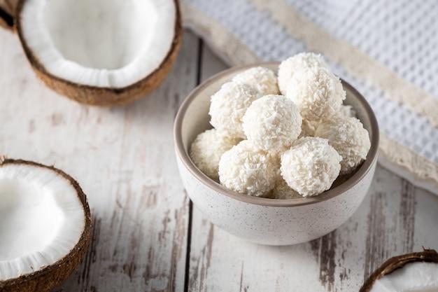 Porties witte chocolade kokosnoot snoep ballen in de kom, rauwe gekraakte kokosnoot