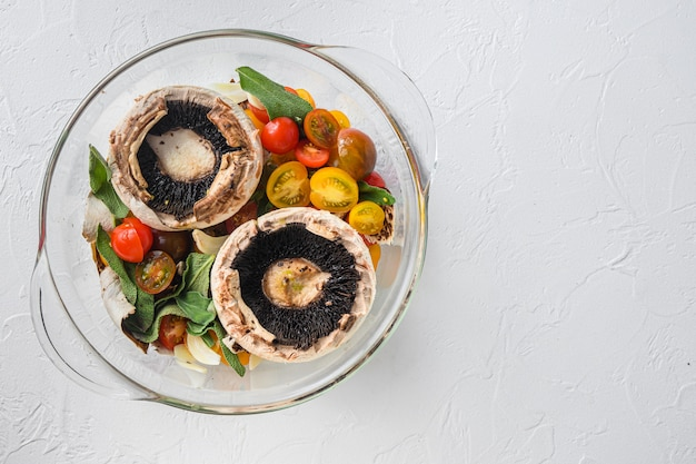 Portobello en ingrediënten voor het bakken van cheddarkaas, kerstomaatjes en salie in glazen pot op witte achtergrond bovenaanzicht concept frame ruimte voor tekst.