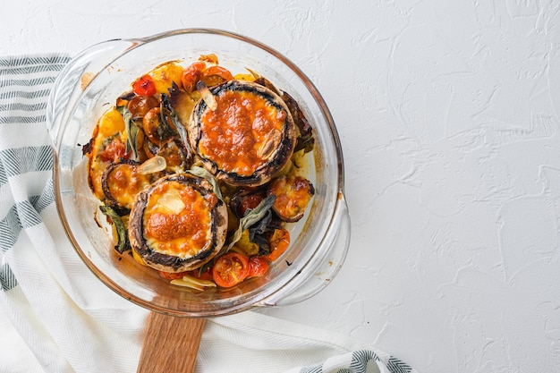 Portobello en ingrediënten voor het bakken van cheddarkaas, kerstomaatjes en salie in pot