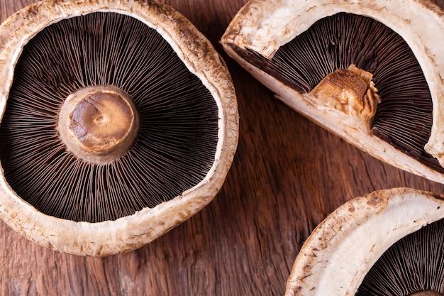 Portobello schiet over oude houten achtergrond als paddestoelen uit de grond
