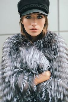 Portrair van modieuze vrouw wandelen in de stad in warme bontjas, winterseizoen, koud weer, zwarte pet, street fashion trend dragen