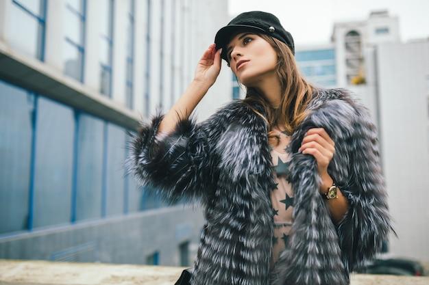Portrair van modieuze vrouw wandelen in de stad in warme bontjas zwarte pet dragen