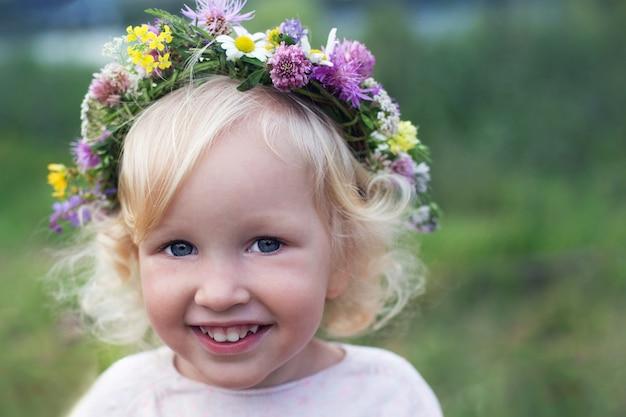 Portraite van klein mooi glimlachend meisje met blond krullend haar en blauwe ogen die wilde bloemenkroon dragen