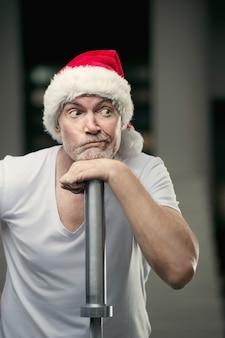 Portraite van senior man in kerstman hoed in sportschool oudejaarsavond en kerst concept