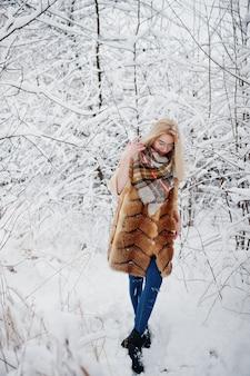 Portraiy van blondemeisje in glazen, rode bontjas en sjaal bij de winterdag.