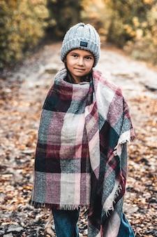 Portrarait van klein meisje bedekt met plaid in de herfst, stijlvolle strik