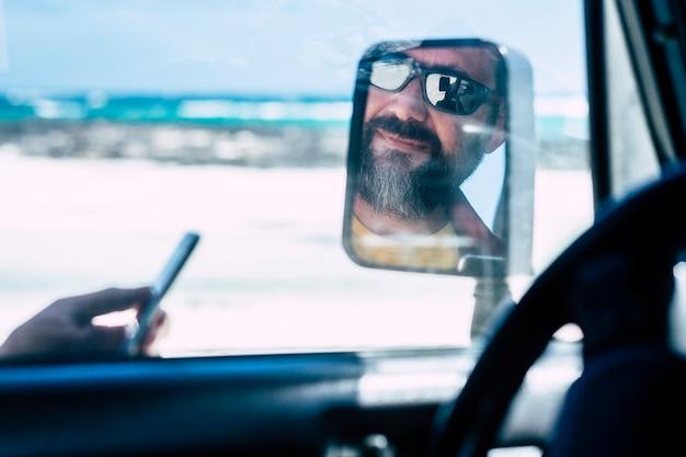 Portrat van het gezicht van de man weerspiegeld en zicht in een autospiegel