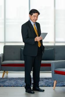 Portret 50s aziatische mannelijke uitvoerende visionaire zakenman met een formeel pak en stropdas, staand binnen kantoor, technologietablet gebruikend, het scherm aanrakend, zelfverzekerd en betrouwbaar glimlachend.