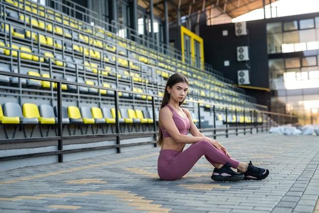 Portret aantrekkelijk meisje in sportkleding die zich voordeed in het stadion voor fitnessoefening. sport- en recreatieconcept voor gezondheid