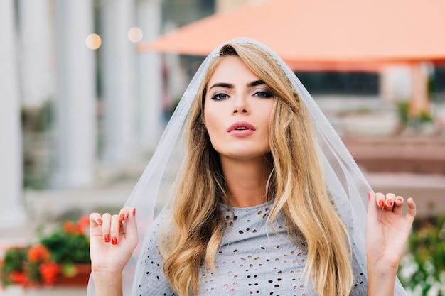 Portret aantrekkelijk meisje met lang blond haar op straat. ze houdt een blauwe sluier vast die haar hoofd bedekt en kijkt naar de camera.