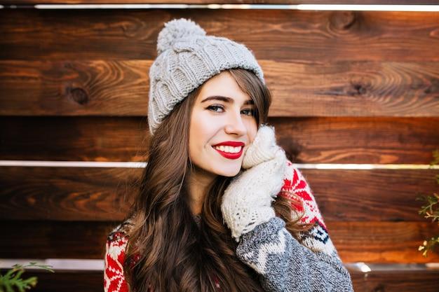 Portret aantrekkelijk meisje met lang haar en rode lippen in gebreide muts op houten. ze raakt gezicht met hand in handschoenen en lacht.