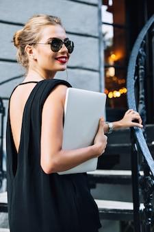 Portret aantrekkelijk model in zwarte jurk met blote rug op trappen buiten. ze glimlacht naar haar kant.