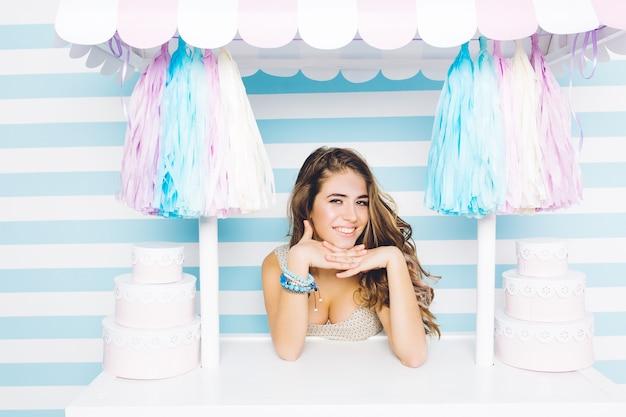 Portret aantrekkelijke jonge vrouw in zomerjurk met lang donkerbruin krullend haar lachend van snoep vrachtwagen op gestreepte muur. blauwe kleuren, feest vieren, snoep, opgewekte sfeer.