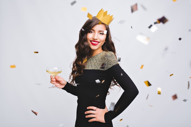Portret aantrekkelijke jonge vrouw met gele kroon verjaardagsfeestje vieren op witte ruimte.