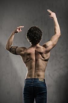 Portret aantrekkelijke sexy narcistische shirtless kerel aantonen zijn biceps in de sportschool
