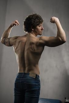 Portret aantrekkelijke sexy narcistische shirtless kerel die zijn bicepsen in gymnastiek aantoont