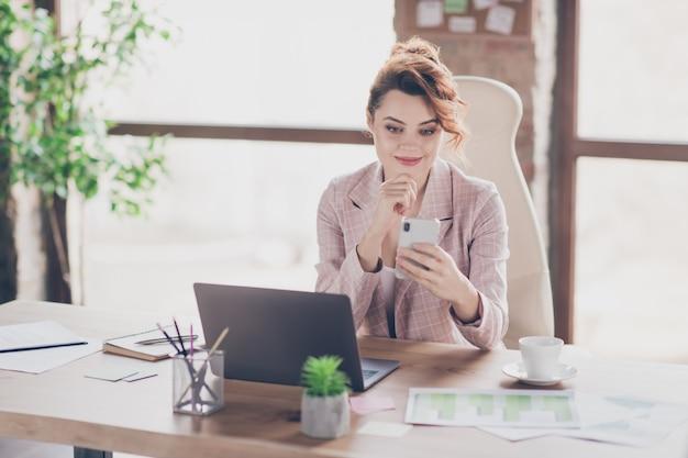 Portret aantrekkelijke stijlvolle dame zittend in stoel sms-telefoon verzenden