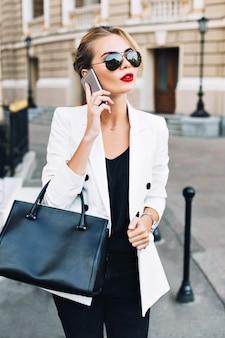 Portret aantrekkelijke vrouw in zonnebril met rode lippen lopen op straat. ze is aan de telefoon.
