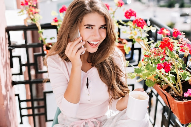 Portret above mooi meisje in pyjama praten over de telefoon op balkon omringen bloemen in zonnige ochtend. ze houdt een kopje vast en glimlacht.