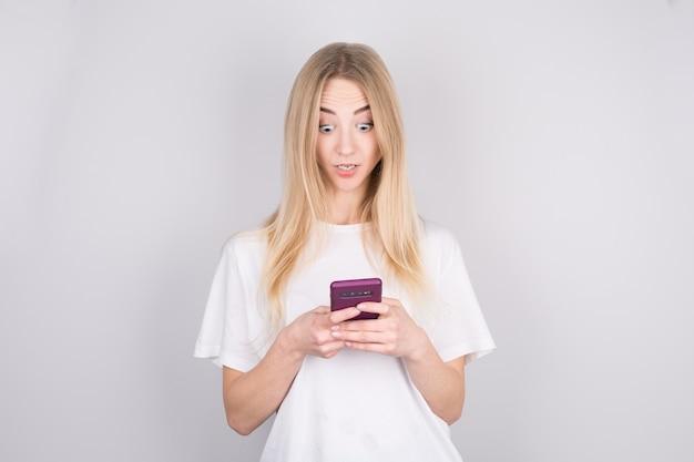 Portret als een geschokt jong meisje dat mobiele telefoon bekijkt die over grijze achtergrond wordt geïsoleerd