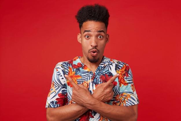 Portret als jonge geschokt afro-amerikaanse man in hawaiiaans shirt, kijkt naar de camera met verbaasde uitdrukking, staat op rode achtergrond, wijst in verschillende richtingen.