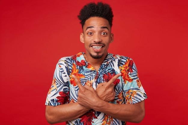 Portret als jonge positieve afro-amerikaanse man in hawaiiaans shirt, kijkt naar de camera met vrolijke uitdrukking, staat op een rode achtergrond en glimlacht in grote lijnen, wijst in verschillende richtingen.