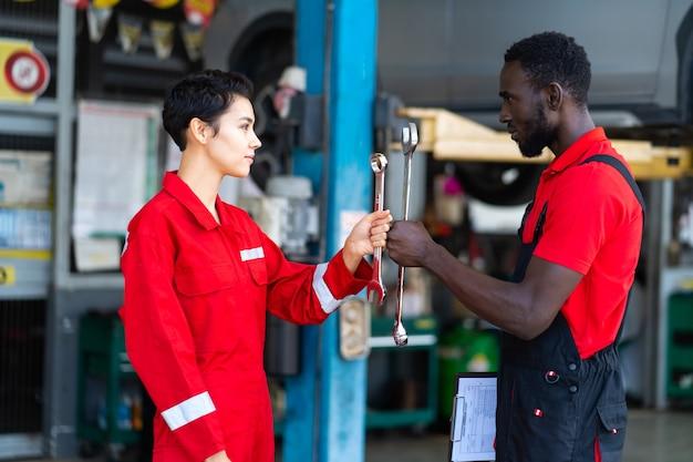 Portret automonteur met moersleutel in de hand. wurggreep. auto reparatie zwarte man en blanke vrouw inspecteur in rood uniform