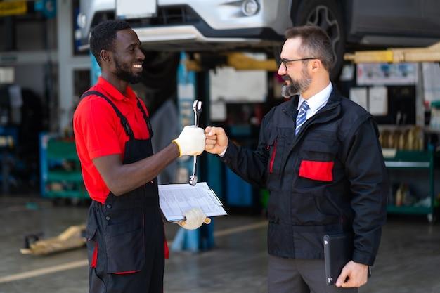 Portret automonteur met moersleutel in de hand. wurggreep. close-up auto reparatie zwarte man hand en blanke man manager of eigenaar.