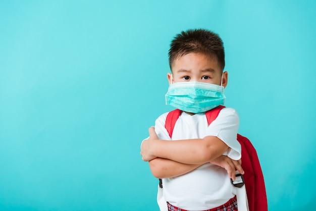 Portret aziaat weinig beschermend gezichtsmasker van de de kleuterschoolslijtage van de kindjongen en schooltas die gekruist wapen bevinden alvorens gaan school