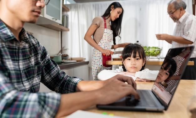Portret aziatisch boos meisje dat haar vader wacht die vanuit huis werkt.