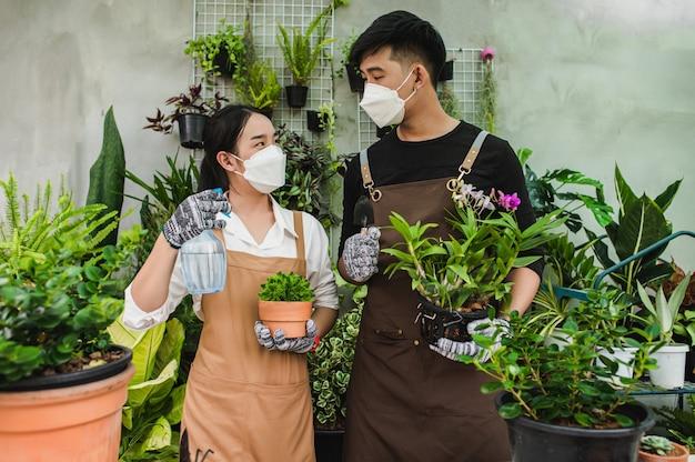 Portret aziatisch jong tuinmanpaar dat een schort draagt, gebruikt tuinapparatuur en helpt de kamerplant in de winkel te verzorgen