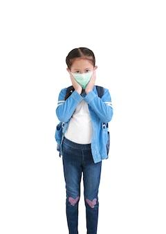 Portret aziatisch klein jong geitjemeisje in toevallige schooluniform die medisch masker met rugzak draagt dat op wit wordt geïsoleerd