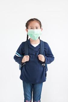 Portret aziatisch klein jong geitjemeisje met het dragen van medisch masker dat op witte achtergrond wordt geïsoleerd