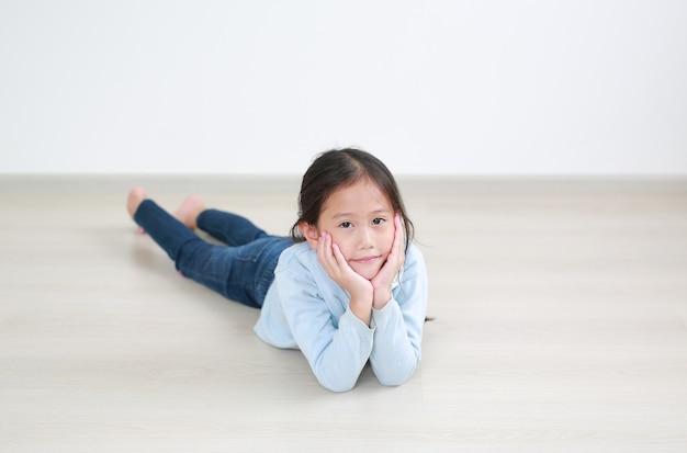 Portret aziatisch klein kindmeisje dat op houten laminaatvloer in de ruimte ligt